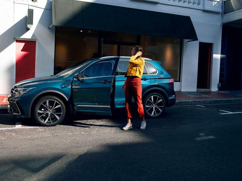 En kvinne står ved den åpne førerdøren til en VW Volkswagen Tiguan SUV
