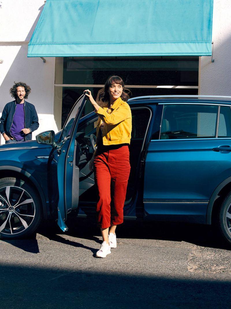 En kvinne går ut av VW Volkswagen Tiguan SUV