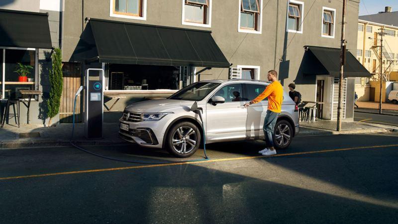 En mann åpner førerdøren på VW Volkswagen Tiguan eHybrid ladbar hybrid