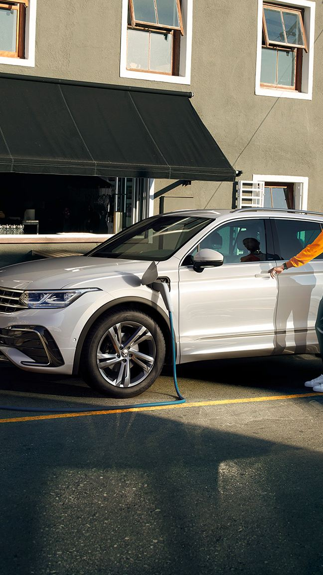 Volkswagen Tiguan hybride rechargeable en blanc, vue latérale, en charge au bord de la route, une personne monte