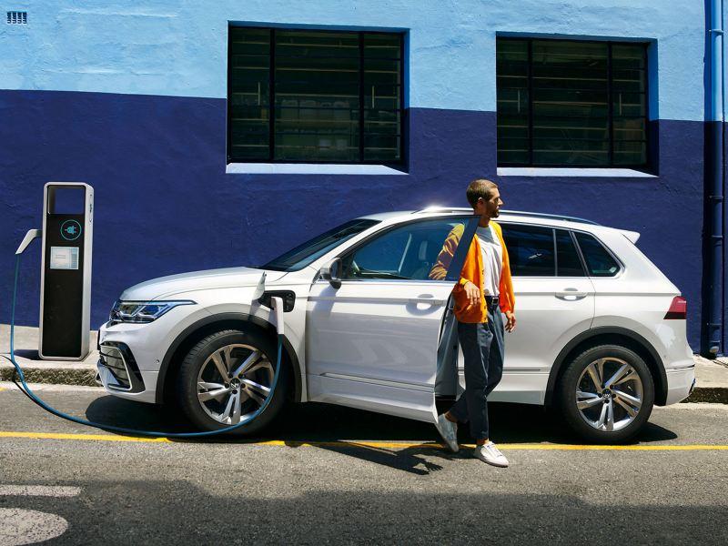 En mann går ut av VW Volkswagen Tiguan eHybrid ladbar hybrid sett fra siden