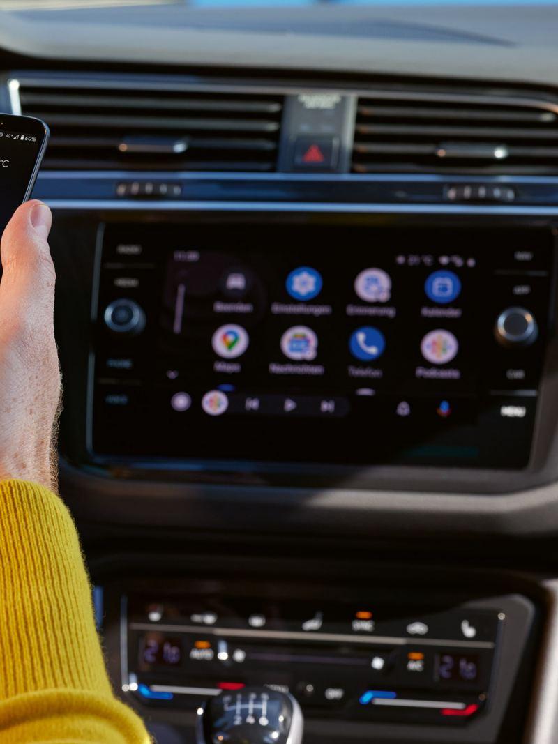 VW Tiguan ACTIVE im Cockpit. Blick auf Smartphone in einer Hand vor dem Farbdisplay mit Bedienfeld. Daneben das Lenkrad.