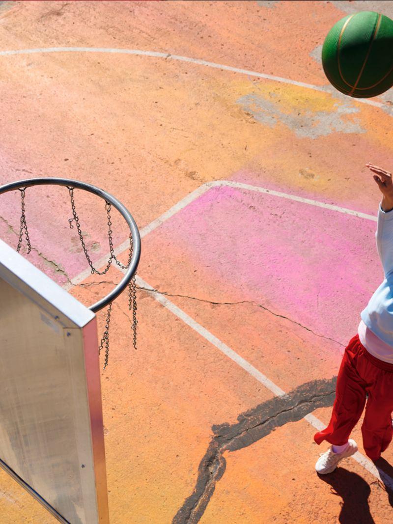 Eine Frau wirft in urbanem Setting einen Basketball in Richtung Korb. Lifestyle.