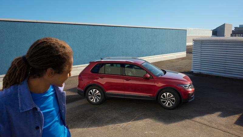Roter VW Tiguan ACTIVE steht in urbaner Umgebung vor einer blauen Wand. In der linken Bildhäfte sieht man einen Mann.