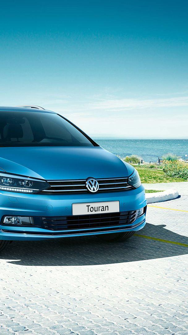 VW Touran, vista anteriore sul parcheggio davanti a un'abitazione in riva al mare