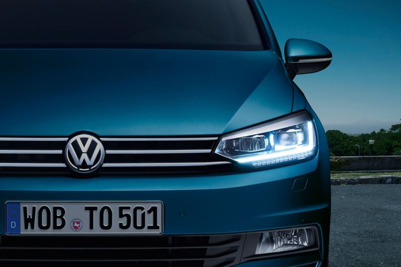 Front of the VW Touran with LED headlight and daytime running light at dusk