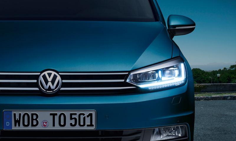 Parte frontale della VW Touran con faro a LED e luce diurna illuminata all'imbrunire