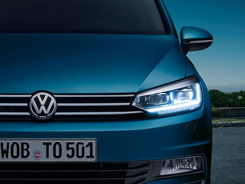 Przód VW Tourana z reflektorami LED i zaświeconymi diodowymi światłami dziennymi po zmroku