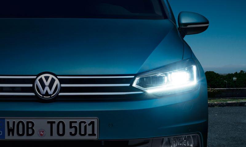 Parte frontale della VW Touran con faro a LED e luce diurna all'imbrunire, illuminati