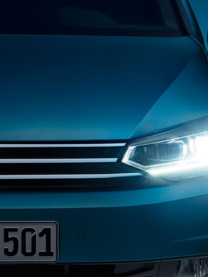 Front of the VW Touran with LED headlight and daytime running light at dusk, illuminated