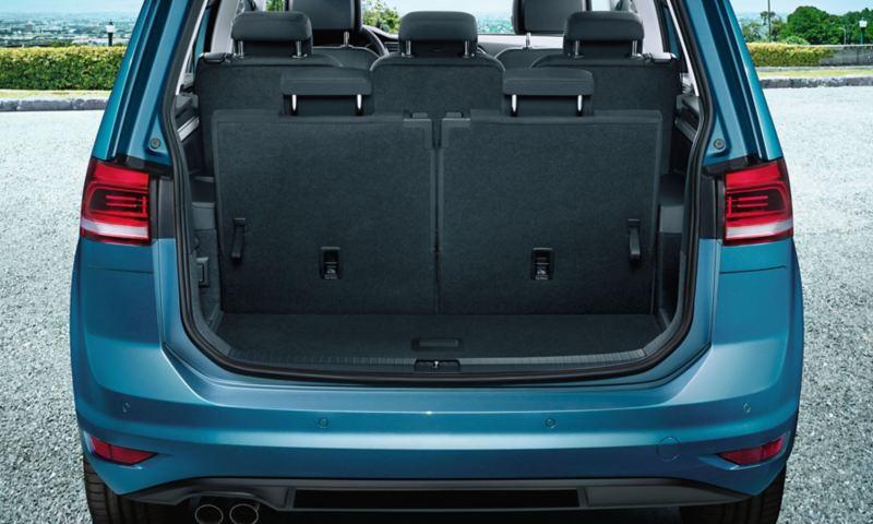 Vista attraverso il portellone posteriore aperto sulla terza fila di sedili di una VW Touran