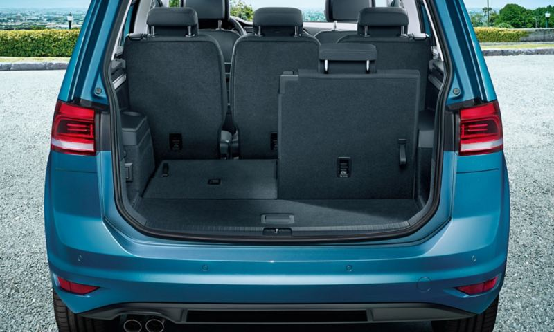 View through open tailgate onto the third row of seats of a VW Touran folded down in the left part