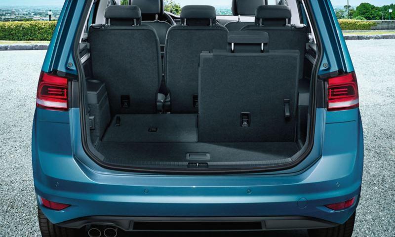 Widok przez otwartą pokrywę bagażnika na trzeci rząd siedzeń ze złożoną lewą częścią w VW Touranie
