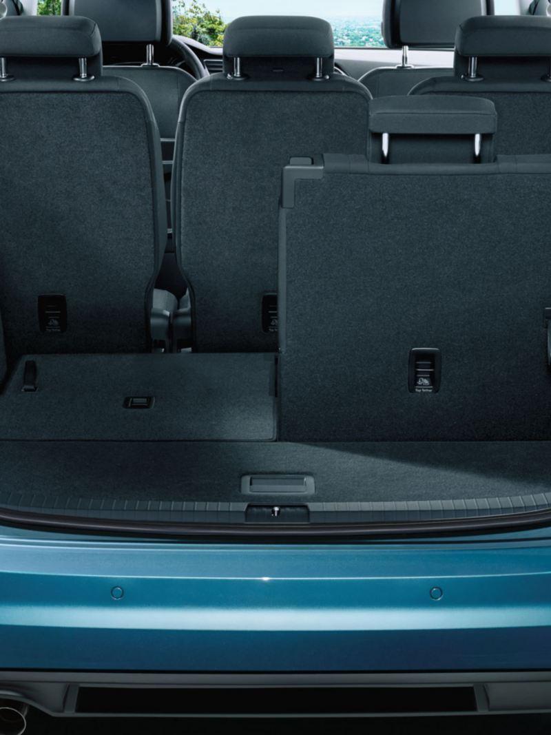 Blick durch geöffnete Heckklappe auf im linken Teil umgeklappte dritte Sitzreihe eines VW Touran