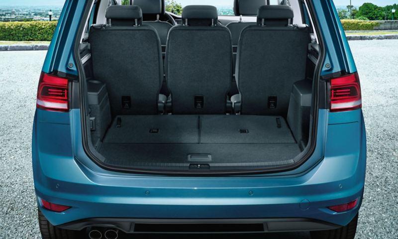 Vista attraverso il portellone posteriore aperto sulla terza fila di sedili completamente ribaltata di una VW Touran