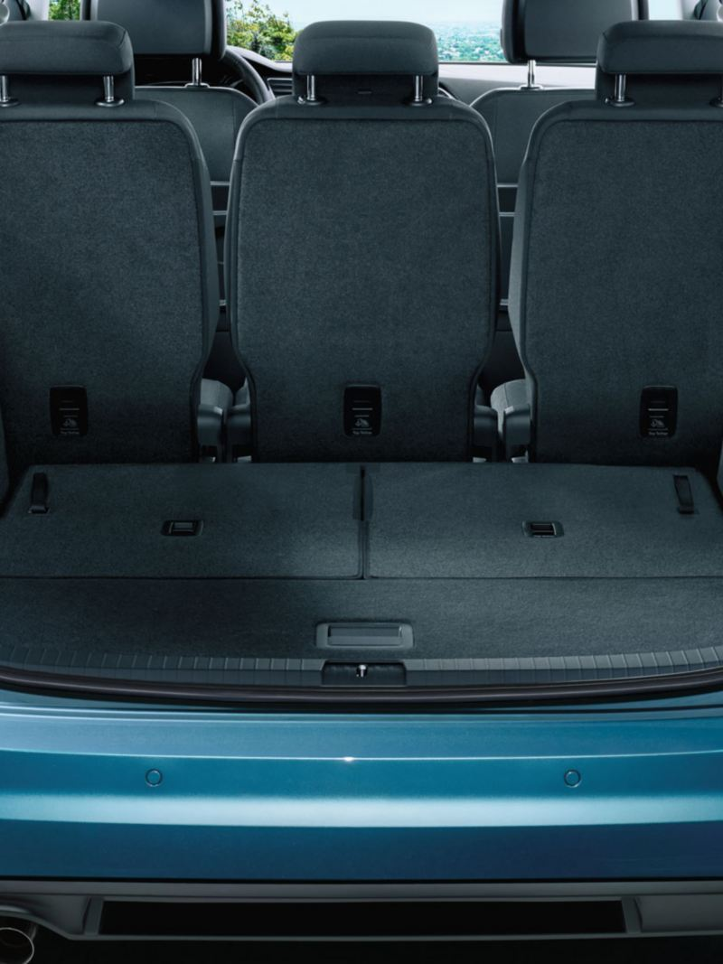 View through open tailgate onto completely folded third row of seats of a VW Touran