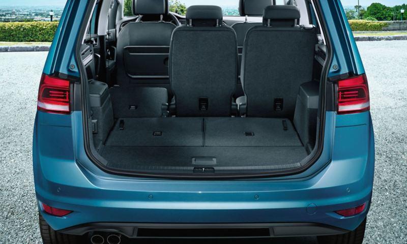 Vista attraverso il portellone posteriore aperto sulla terza fila di sedili completamente ribaltata e sedile sinistro ribaltato della seconda fila di sedili di una VW Touran