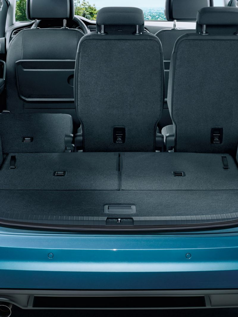 View through open tailgate to completely folded down third row of seats and folded down left seat of the second row of seats of a VW Touran