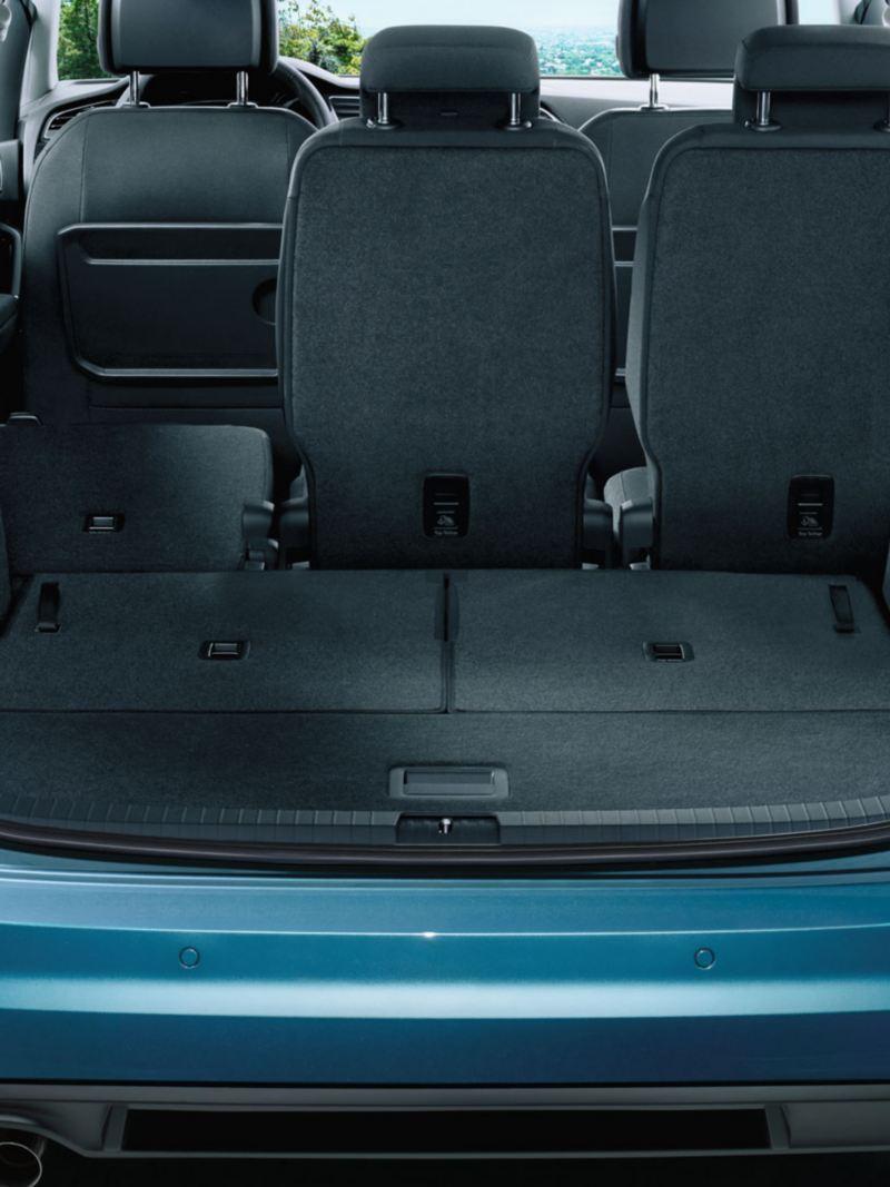 Blick durch geöffnete Heckklappe auf komplett umgeklappte dritte Sitzreihe und umgeklappten linken Sitzplatz der zweiten Sitzreihe eines VW Touran