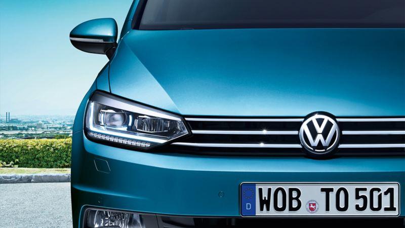 VW Touran von vorne mit Scheinwerfer mit LED-Tagfahrlicht auf einem Parkplatz, im Hintergrund ein Industriegebiet