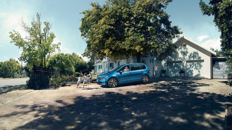 Volkswagen Touran parkert foran hus med barn løpende foran