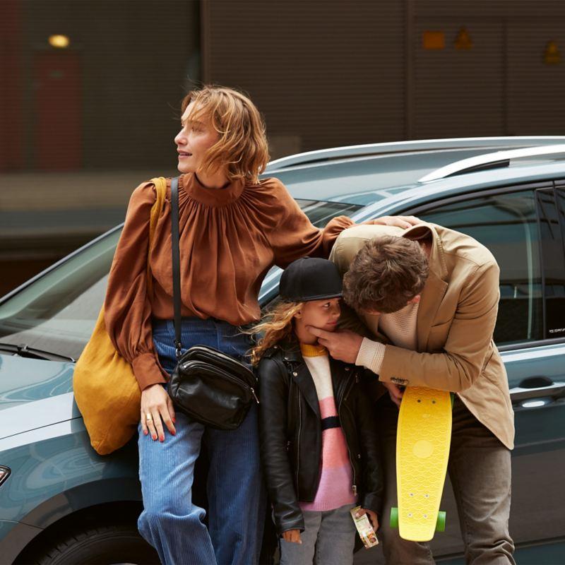 Ojciec, matka i córka opierają się o Tourana IQ.DRIVE