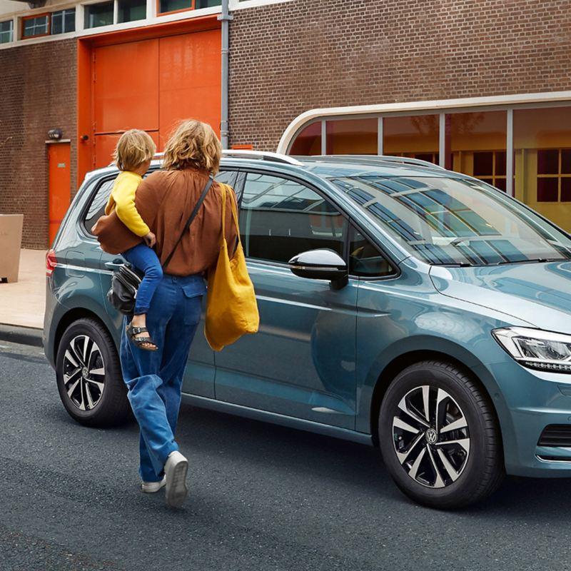 Mutter mit Kind auf dem Arm geht in Richtung eines parkenden VW Touran in blau.