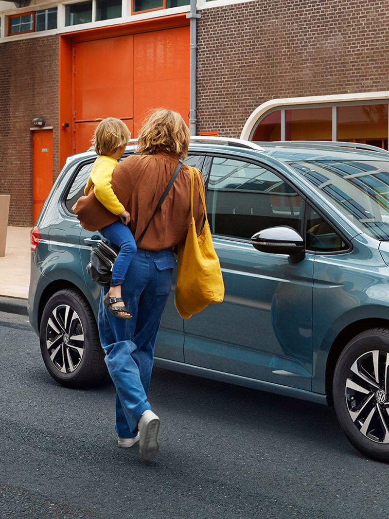 Eine Frau trägt ihr Kind zu ihrem Volkswagen