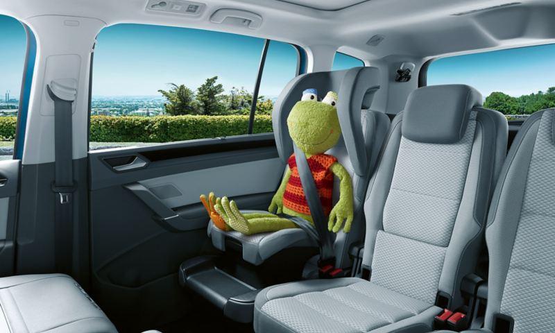 Siège enfant intégré à la banquette arrière d'une VW Touran avec une grenouille en peluche attachée.