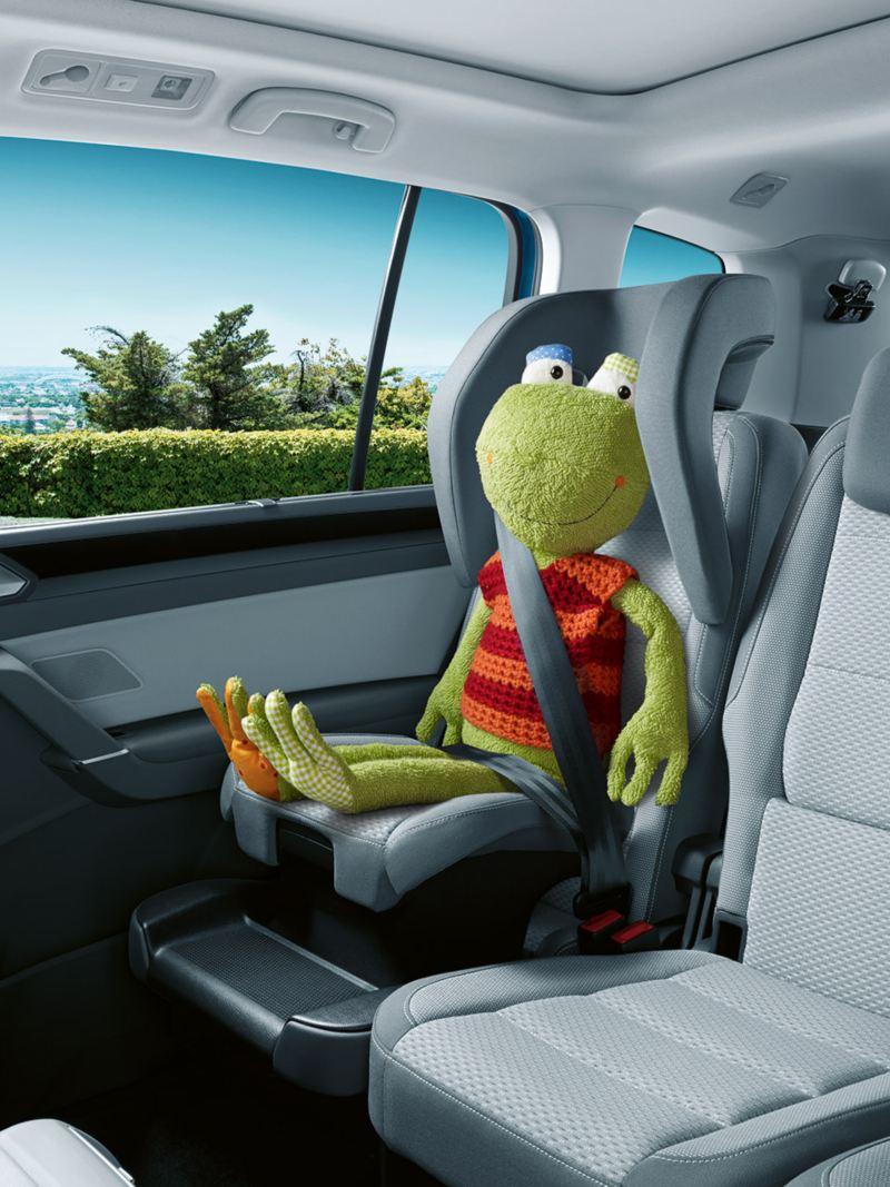Zintegrowany fotelik dziecięcy na tylnej kanapie VW Tourana z przypiętą maskotką - żabą