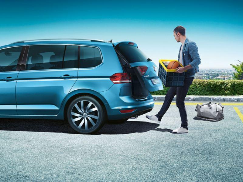 Un homme portant une caisse se trouve à l'arrière du VW Touran et effectue un mouvement du pied; «Easy Open» ouvre le hayon