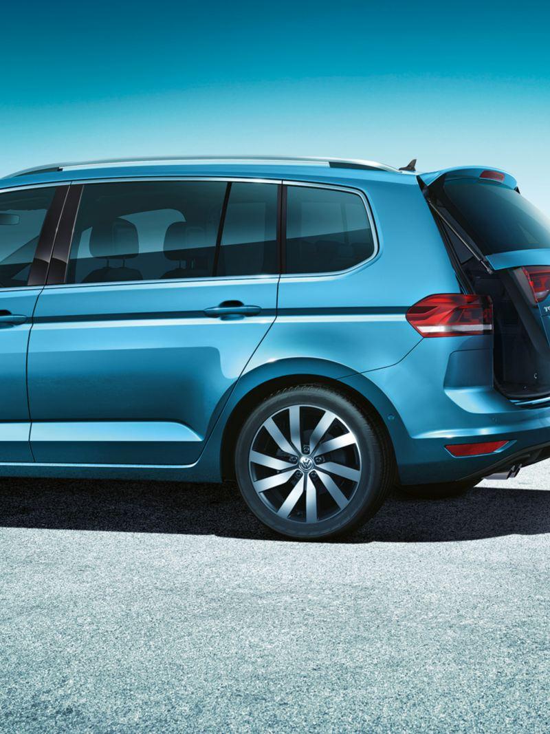 """Ένας άντρας με κιβώτιο μεταφοράς στο πίσω μέρος του Volkswagen Touran κάνει μια κίνηση με το πόδι. Το """"Easy Open"""" ανοίγει το πίσω καπό"""