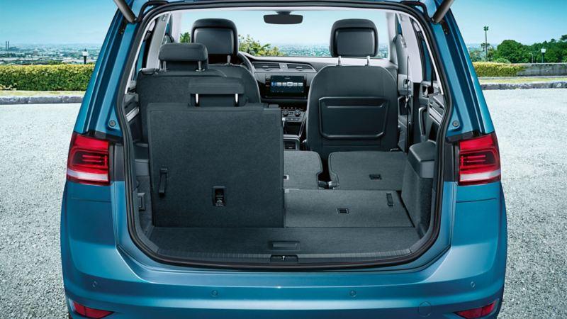 VW Touran widziany od tyłu z otwartym bagażnikiem. Prawe siedzenie tylnego rzędu jest złożone.