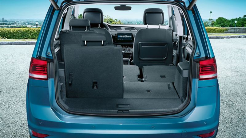VW Touran von hinten betrachtet mit Blick in den geöffneten Kofferraum. Der rechte Sitz der hinteren Reihe ist umgeklappt