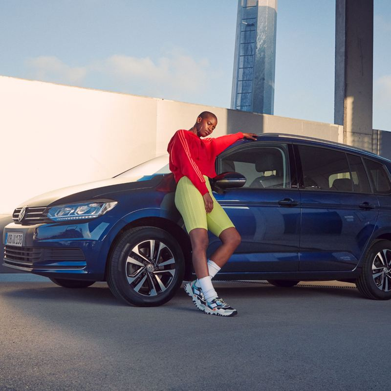Frau lehnt an VW Touran UNITED Kotflügel
