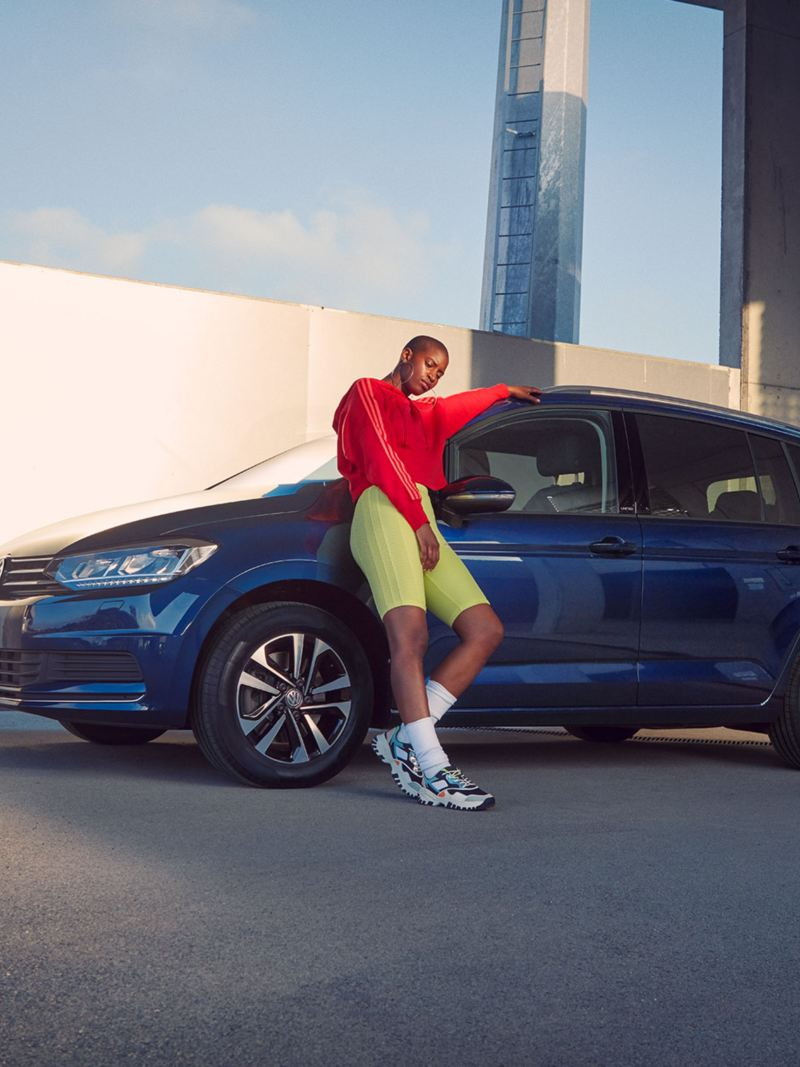 Mann lehnt an Kotflügel von VW Touran UNITED