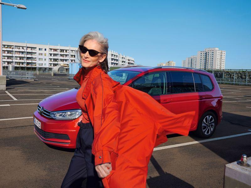 Roter VW Touran ACTIVE auf urbanem Parkplatz. Stadt im Hintergrund. Blick auf Leuchten und Seite. Davor Frau mit roter Jacke.