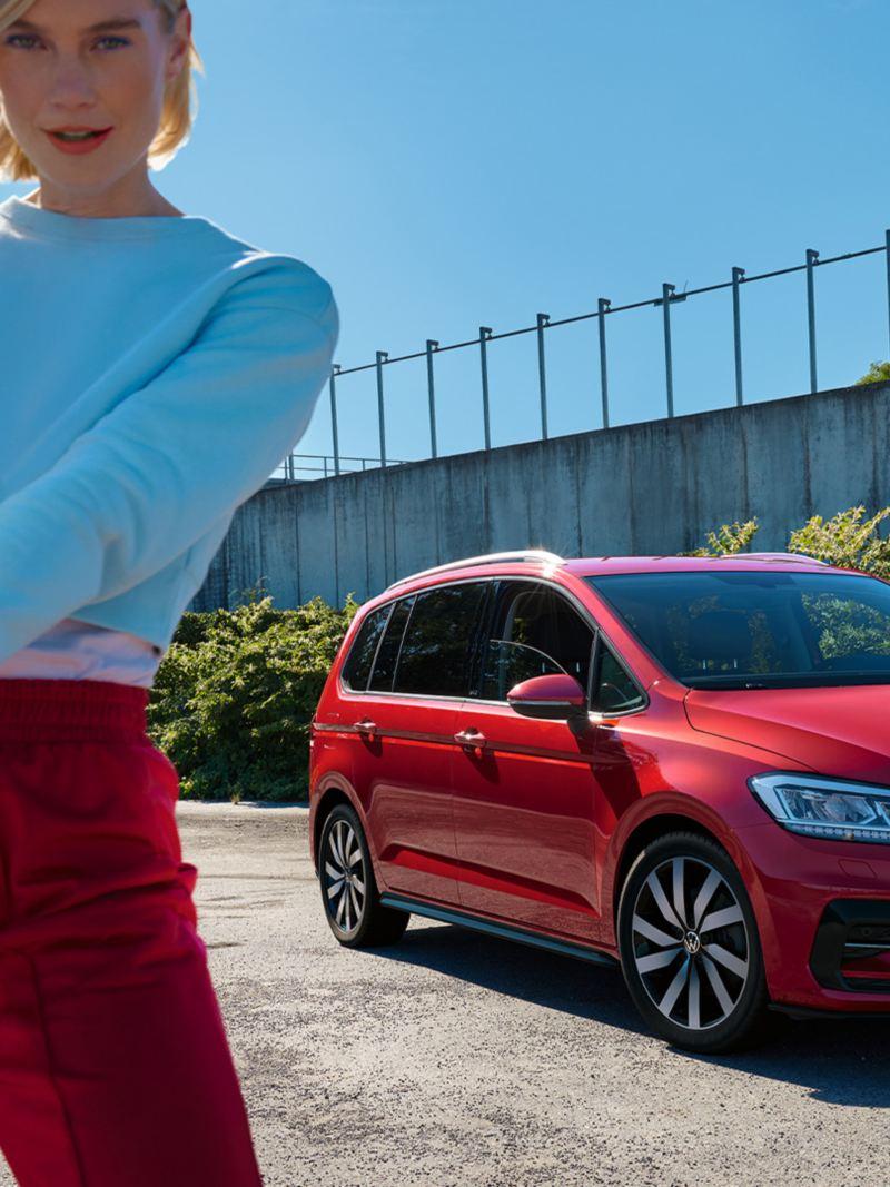 VW Touran rouge ACTIF dans un parking urbain. Ville en arrière-plan. Vue des lumières et de l'avant. Une femme en veste rouge devant.