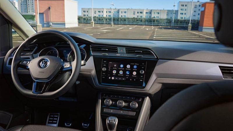 Intérieur du VW Touran ACTIVE. Vue sur le cockpit avec volant multifonctions, écran couleur, sièges et pédales.