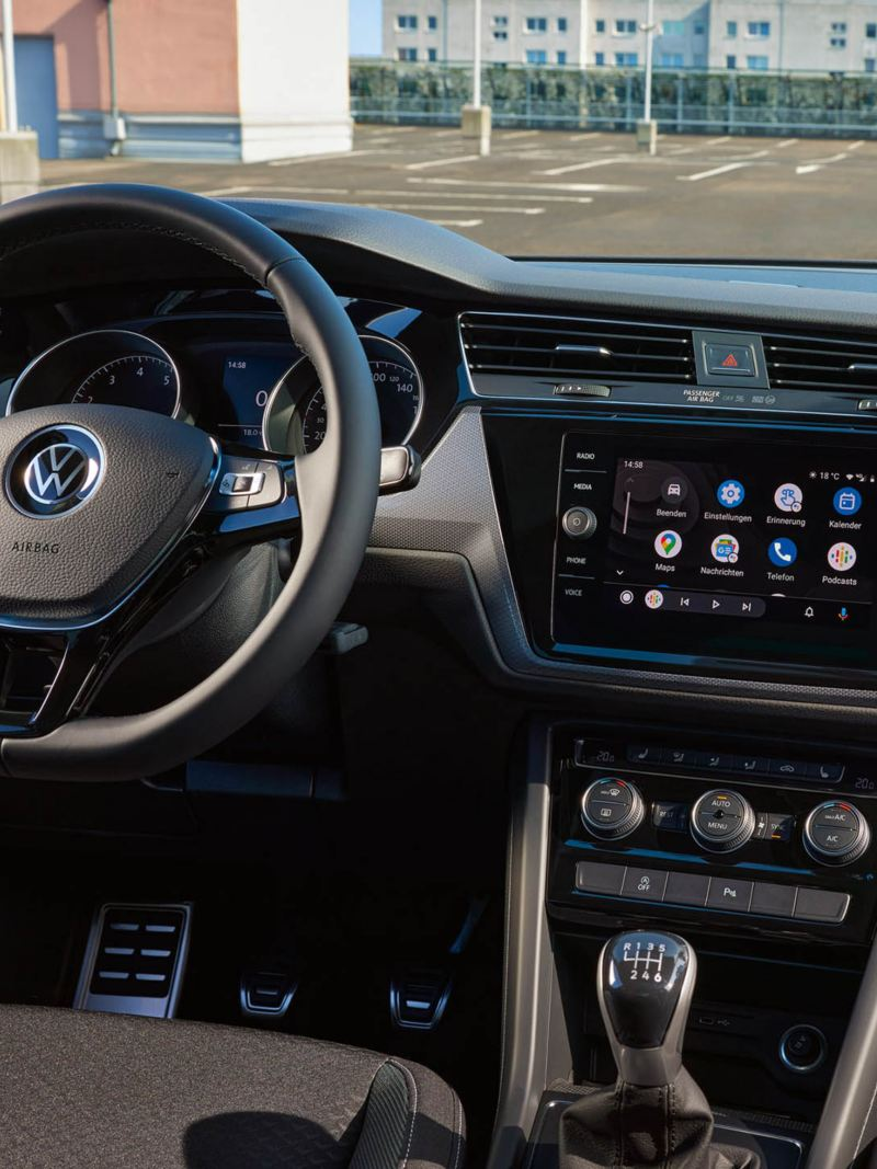 VW Touran ACTIVE innen. Blick ins Cockpit mit Multifunktionslenkrad, Farbdisplay, Sitzen und Pedalen.
