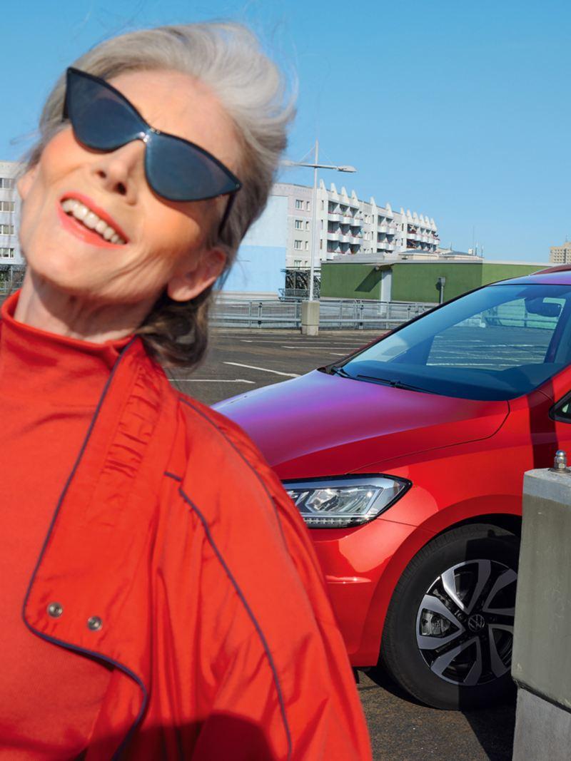 Roter VW Touran ACTIVE auf urbanem Parkplatz. Stadt im Hintergrund. Blick auf Leuchten und Front. Davor Frau mit roter Jacke.