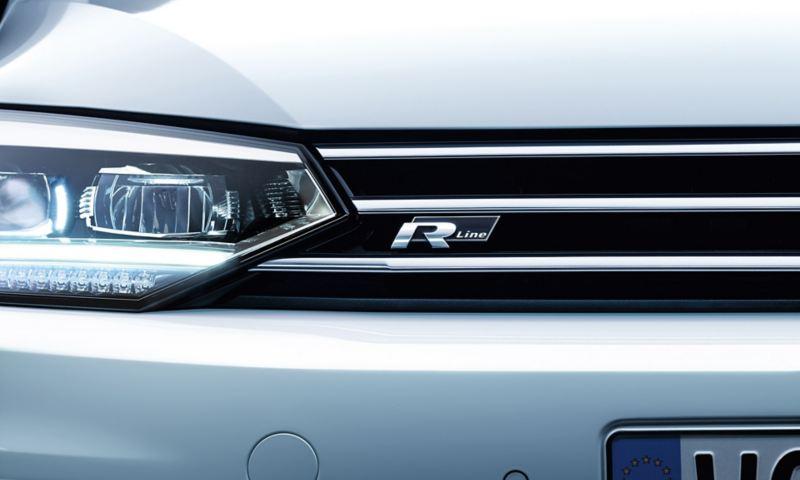"""Detail der Front des VW Touran mit angeschnittenen Scheinwerfern und """"R-Line""""-Logo am Kühlerschutzgitter"""