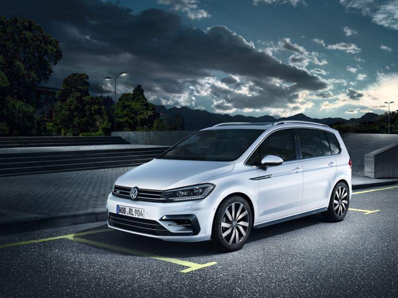 VW Touran mit R-Line Ausstattungen schräg von vorne auf Parkplatz stehend