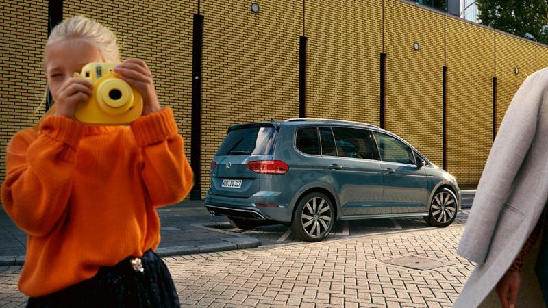 Dziewczynka z polaroidem, w tle Touran IQ.DRIVE