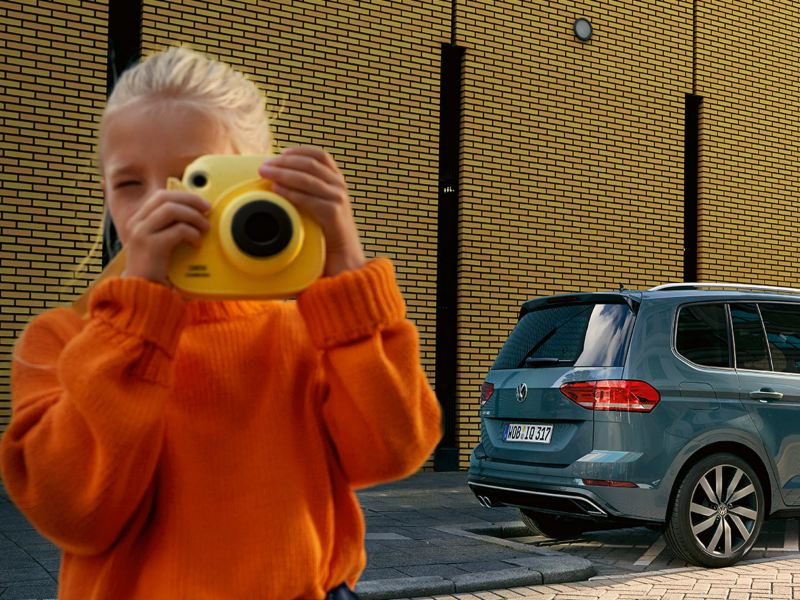 Mädchen mit Polaroidkamera vor einem VW