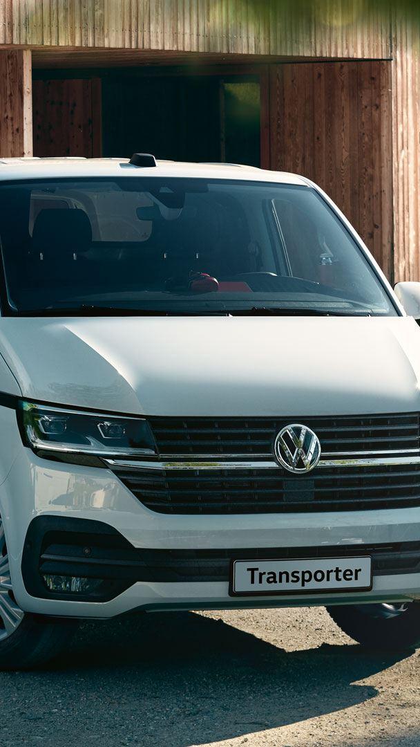 Vista 3/4 frontale di Transporter Furgone Volkswagen mentre esce da un garage. Sullo sfondo un lavoratore trasporta delle assi di legno.