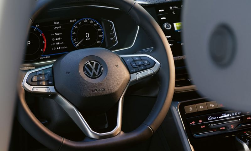 Multifunction steering wheel and Active Info Display in the new VW T-Cross; part of the B-pillar and headrest are visible in the foreground