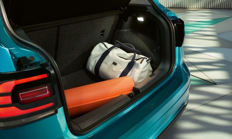 Ανοιχτός χώρος αποσκευών του Volkswagen T-Cross με τυλιγμένο στρώμα γυμναστικής και αθλητική τσάντα