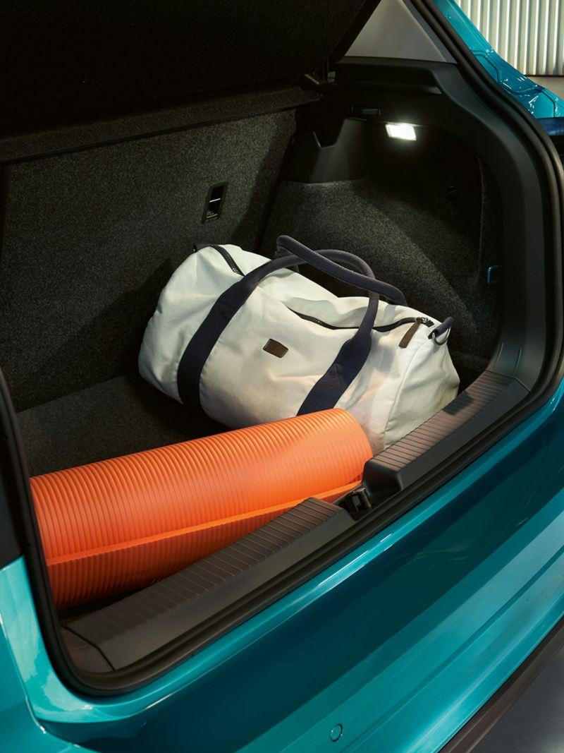 Geöffneter Kofferraum des VW T-Cross mit gerollter Gymnastikmatte und Sporttasche