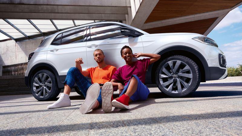Due ragazzi seduti e appoggiati di spalle ad una vettura Volkswagen